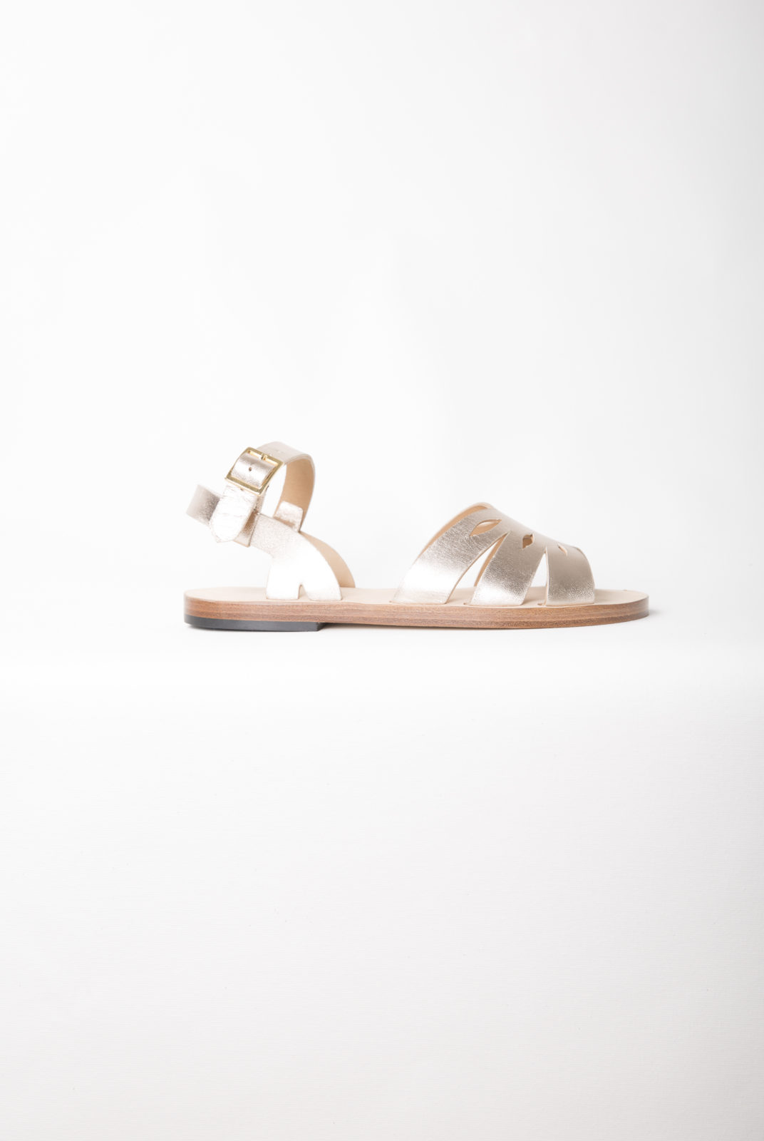 Cuir métallisé. Bout arrondi. Chaussures ouvertes. Large bandeau ajouré au cou-de-pied. Découpes florales.