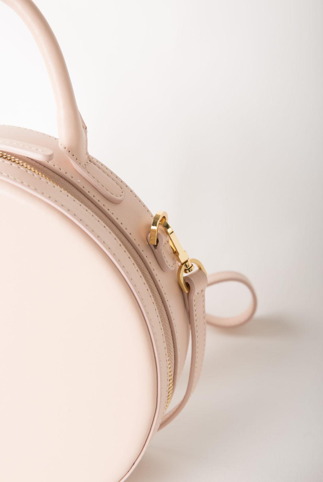 Sac cercle rose clair en cuir de veau italien avec intérieur en daim rose clair. Deux poches intérieures et fermeture à glissière. Fabriqué en Italie.