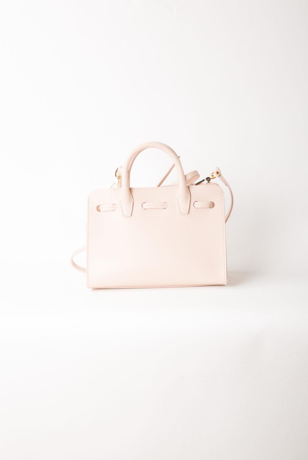 Mini sac de soleil mini rose italien en cuir de veau rose clair avec intérieur verni mat rose clair. Poche latérale intérieure et bandoulière réglable détachable. Fabriqué en Italie.